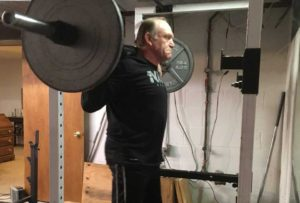 An adult squatting in a squat rack